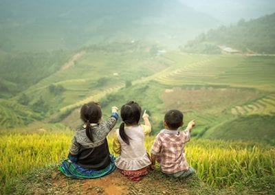 Three children sitting side by side, back view to point to Rice
